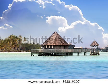Lodges over transparent quiet sea water- tropical paradise - stock photo