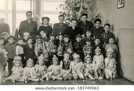 LODZ, POLAND, CIRCA DECEMBER 1970's: Vintage photo of group of children posing with their tutors and parents near Christmas tree - stock photo
