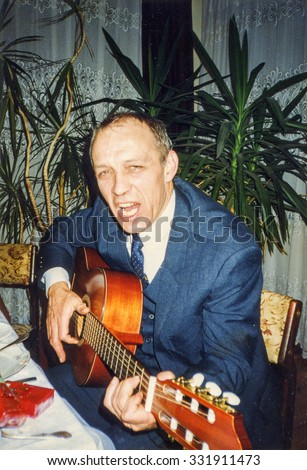 LODZ, POLAND, CIRCA 1990: Vintage photo of man playing guitar and singing during a family party - stock photo