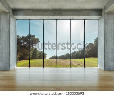Lofty house with wooden floor and large windows in the countryside - stock photo
