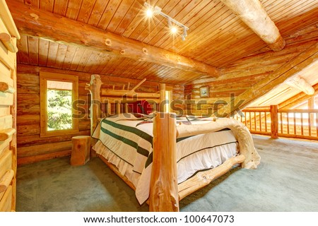 Log cabin bedroom under wood large ceiling with queen size bed. - stock photo