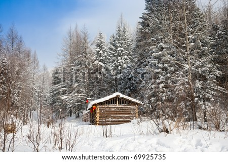 log cabin in winter forest - stock photo