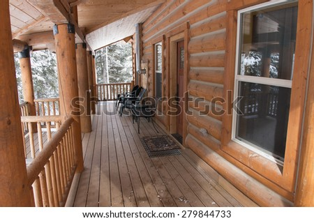 Log cabin porch in the snow - stock photo