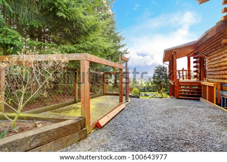 Log cabin with dogs fenced canal area behind the house. - stock photo