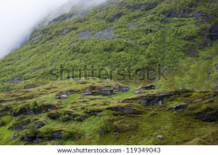 Log cabins on hillside of Norway mountains - stock photo