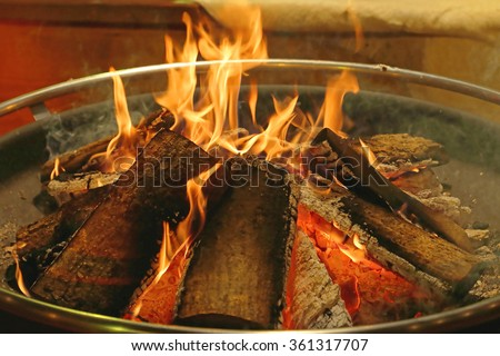 Log Fire in Circular Metal Firepit Tray - stock photo