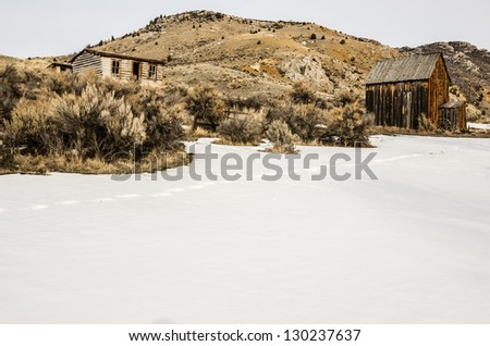 Log home on a hill with a barn or storage building nearby on a winter day at Bannack State Park in Montana. - stock photo