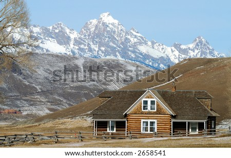 Log house on prarie with snow covered Gand Teton mountains in background - stock photo
