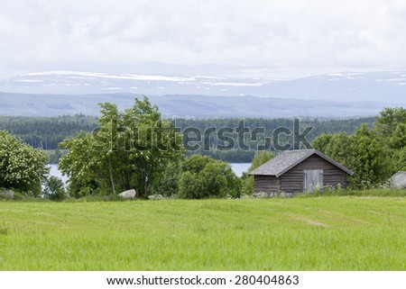 Log, timber barn on the farmland, landscape. Great-Lake area and mountains in the background. - stock photo
