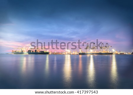 Logistic Import Export background, Container Cargo freight ship with working crane bridge in shipyard at dusk - stock photo