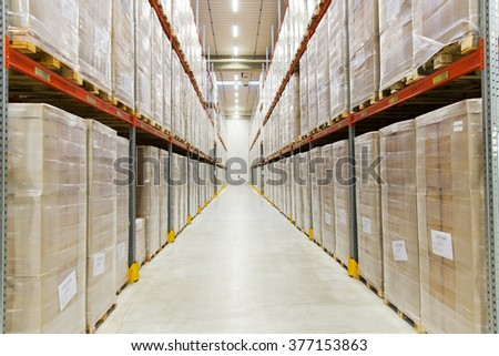 logistic, storage, shipment, industry and manufacturing concept - cargo boxes storing at warehouse shelves - stock photo