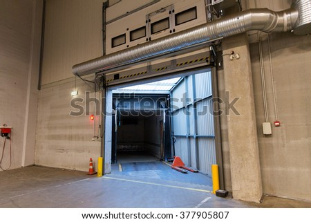 logistic, storage, shipment, transportation and loading concept - warehouse door or gate and truck container - stock photo