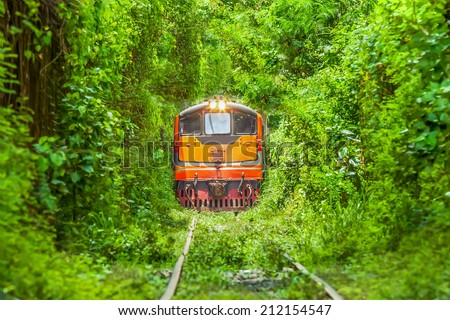 Logistic Train running on Natural Train tree tunnel in Thailand (Bangkok) - stock photo