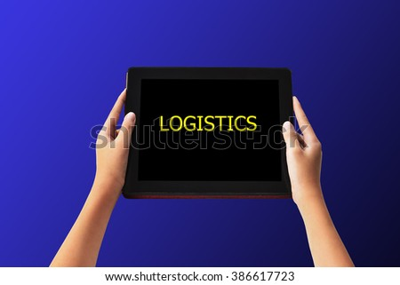 """Logistics Concept. """"LOGISTIC"""" words in yellow color on tabled in hands on blue color background. - stock photo"""