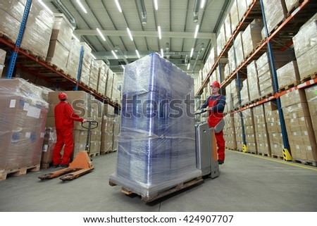 Logistics - two workers in uniforms and safety helmets working in storehouse - stock photo