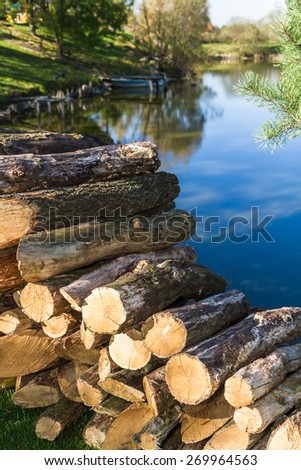Logs of wood stacked. Lake background. - stock photo