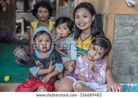 Loko, Sulawesi, Indonesia - August 17, 2014: Indoor portrait of a cute family, two adult women and two babies, in the village of Loko, Mamasa region, West Tana Toraja. - stock photo