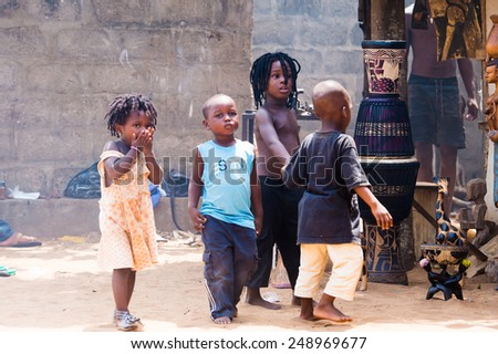 LOME, TOGO - MAR 9, 2013: Unidentified Togolese children play in the street. People of Togo suffer of poverty due to the unstable economic situation. - stock photo