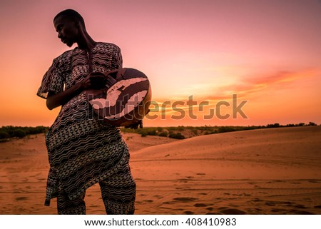 LOMPOUL/SENEGAL - NOVEMBER 12, 2013: Lonely unidentified african musician playing drum at the sunset in Lompoul desert, Senegal - stock photo