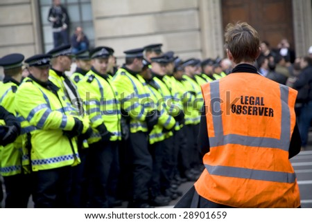 LONDON - APRIL 1 : A volunteer legal observer watches police conduct during G20 protests April 1, 2009 in London. 35,000 people join the demonstrator in Central London. - stock photo