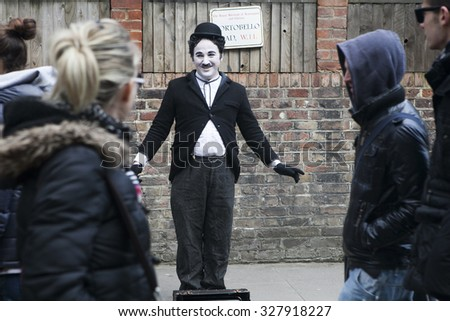 LONDON - APRIL 12: An unidentified artist looks like Charlie Chaplin performs on April 12, 2013 in Portobello Road, London.  - stock photo