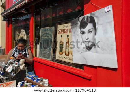 LONDON - APRIL 1: An unidentified woman sells souvenirs to tourists on April 1, 2007 in Camden Town, London. Camden, well known for its markets, is visited by 100.000 people each weekend. - stock photo