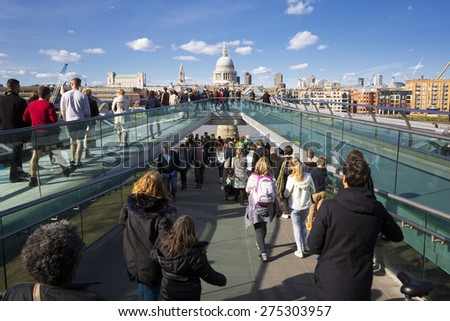 LONDON-APRIL 11 :People walking across a footbridge Millennium Bridge. Background is St Paul's cathedral in London. Bridge was opened 10 June 2000. View on April 11, 2015 - stock photo