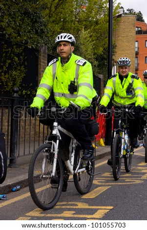 LONDON - APRIL 22: Police officers on bicycles during the London marathon on April 22, 2012 in London, England, UK. The marathon is an annual event - stock photo