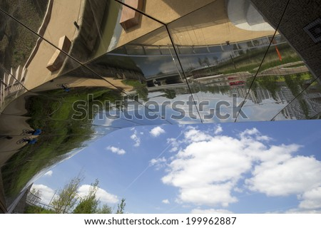 LONDON - APRIL 5. Reflections in mirrored underside of bridge at the Queen Elizabeth Olympic Park on April 5, 2014, opening day of the new public area in London, UK - stock photo