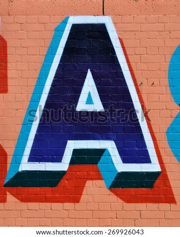 LONDON -APRIL 11, 2015. Typographic street art on brickwork in Braithwaite Street at Shoreditch in the Borough of Tower Hamlets, an area renown for its public art in east London, UK. - stock photo