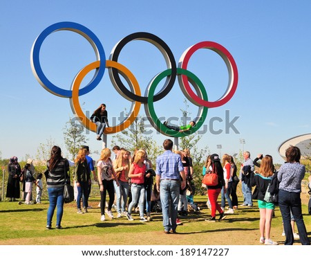 LONDON - APRIL 16. Visitors enjoying the Olympic Games symbol in the new Queen Elizabeth Olympic Park, on April 16, 2014, a legacy from the games in the parkland now open at Stratford, London, UK. - stock photo