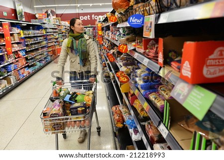 LONDON - AUG 18: A shopper browses an aisle at an Asda supermarket on Aug 18, 2014 in London, UK. Asda is the UK's third largest retail chain with 568 stores and an operating income of �£638 million. - stock photo
