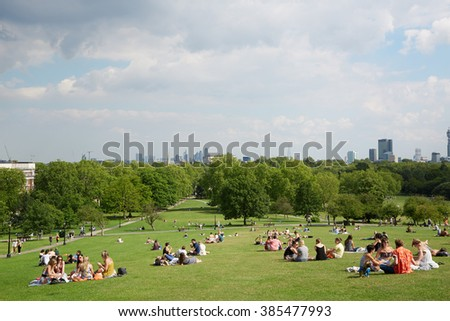 LONDON - AUGUST 8: Primrose hill top with London city view and people relaxing in the park on August 8, 2015 in London. Primrose hill is now one of most exclusive residential area in London. - stock photo