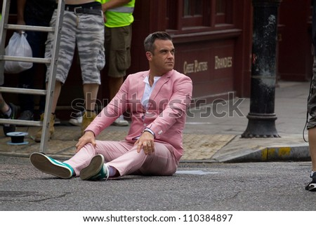 LONDON - AUGUST 16: Robbie Williams records the music video for his new song in Londons Spittalfields Market, August 16, 2012 in London, Uk - stock photo
