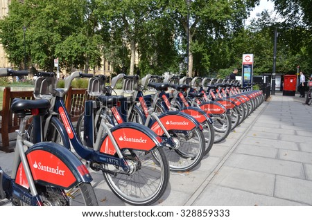 "LONDON - AUGUST 6: The bicycles at this rental station near London's Parliament, shown on August 6, 2015, are nicknamed ""Boris bikes"" after London Mayor Boris Johnson.  - stock photo"