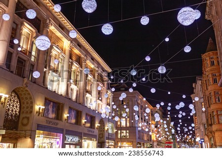 LONDON - DEC 14 : Christmas Lights Display on Oxford Street on December 14th, 2014, London, UK. The modern colorful Christmas lights attract and encourage people to the street.  - stock photo