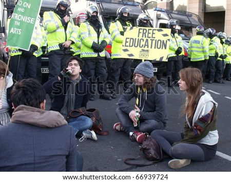 LONDON - DEC 9: Students demonstration against university fee rises in front of police lines at the houses of parliament buildings London, dec 9, 2010. - stock photo