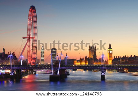 LONDON - DECEMBER 8: The London Eye and Houses of Parliament in London, England on December 8, 2012. The London Eye is the most popular paid tourist attraction in the United Kingdom. - stock photo