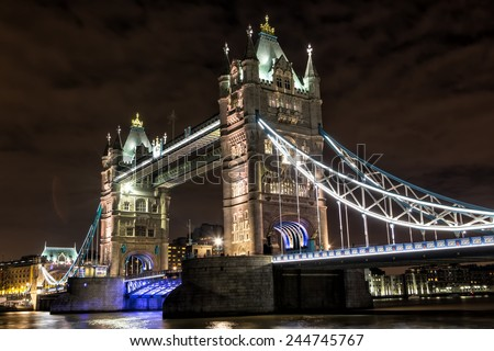 LONDON - DECEMBER 31: Tower Bridge at night on December 31, 2014. Tower Bridge (built 1886-1894) is a combined bascule and suspension bridge in London which crosses the River Thames. - stock photo