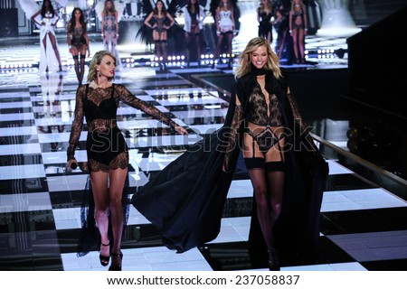 LONDON, ENGLAND - DECEMBER 02:  Taylor Swift (L) performs as model Karlie Kloss walks the runway during the 2014 Victoria's Secret Fashion Show on December 2, 2014 in London, England. - stock photo