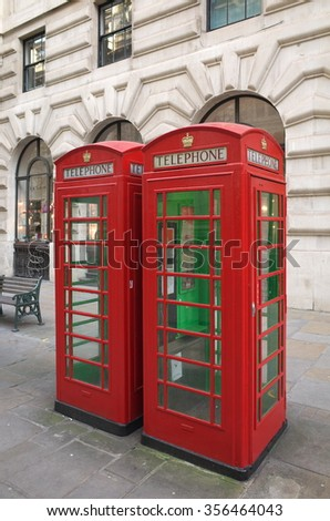 London, England - December 28, 2015: Two traditional red telephone boxes in Central London, England. The original kiosks were first introduced to Britain in 1921 - stock photo