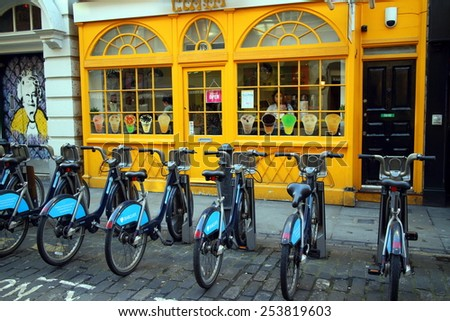 London, England - February 17, 2015: Barclays Bank bicycles parked in a row front of a colorful cafe in London, England. The rental scheme provides over 5000 bikes for hire across the city. - stock photo