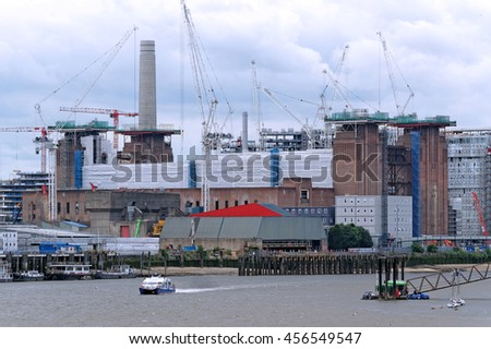 LONDON, ENGLAND - JULY 8, 2016: Construction cranes over the Battersea power station currently being rebuilt, and transformed into luxury housing, shops and entertainment in London, England. - stock photo