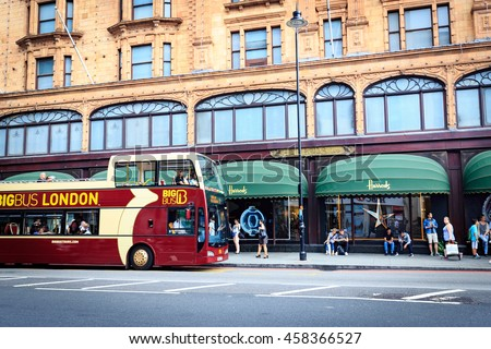 LONDON, ENGLAND - JULY 20, 2016. Exterior of Harrods department store in the Brompton Road, Knightsbridge showing shoppers passing by. - stock photo