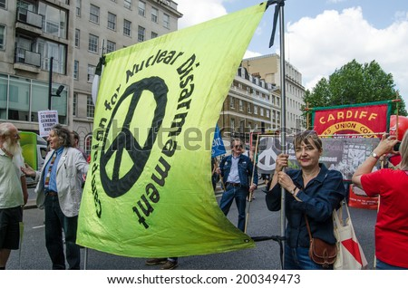 LONDON, ENGLAND - JUNE 21, 2014:  Campaign for Nuclear Disarmament General Secretary Kate Hudson, holding the group's banner during a march through London campaigning against the Coalition Government. - stock photo