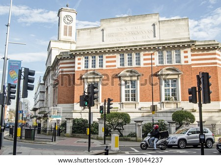 LONDON, ENGLAND - MARCH 15, 2014: Acton Town Hall in the centre of the West London suburb with traffic waiting at a junction. - stock photo