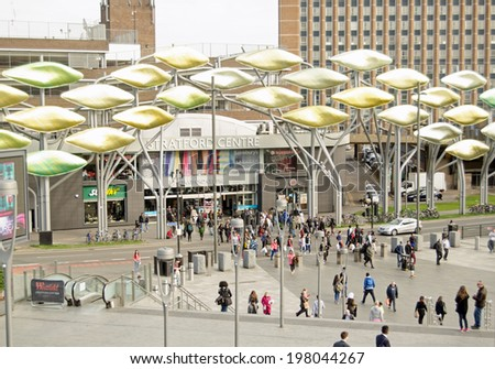 LONDON, ENGLAND - MARCH 17, 2014: Pedestrians walking between the Stratford Centre and the main railway station in Newham, East London. - stock photo