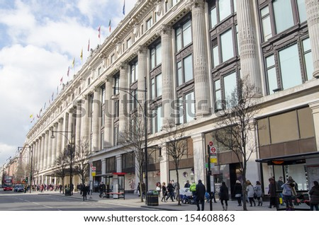 LONDON, ENGLAND - MARCH 13: Shoppers walking past the famous Selfridges Department Store on Oxford Street, central London on March 13 2013.  The street is home to many fashion shops. - stock photo