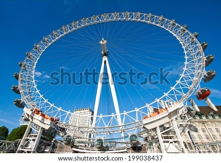 London, England - May 25, 2014: London Eye is a famous tourist attraction at a height of 135 metres (443 ft) the biggest Ferris wheel in Europe. - stock photo