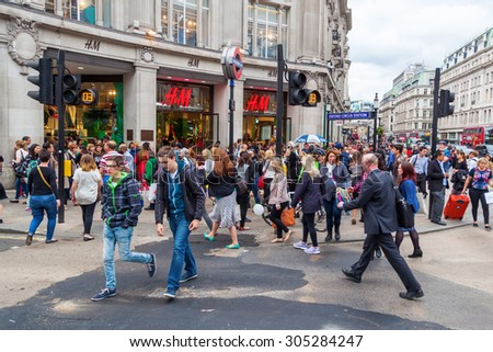 LONDON, ENGLAND - MAY 20, 2014: Oxford Circus with unidentified people in London. Up to over 40.000 pedestrians per hour pass the junction, it is the highest pedestrian volumes recorded in London. - stock photo